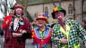 Drei Clowns vor einer Kirche