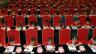 Schulkinder in China nehmen an einem akademischen Wettbewerb teil, sie sitzen reihenweise hintereinander, auf roten Stühlen und alle in denselben roten T-Shirts, sie sind am Schreiben.